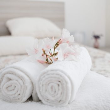 White and fresh laundered fluffy towels with flower on bed in hotel